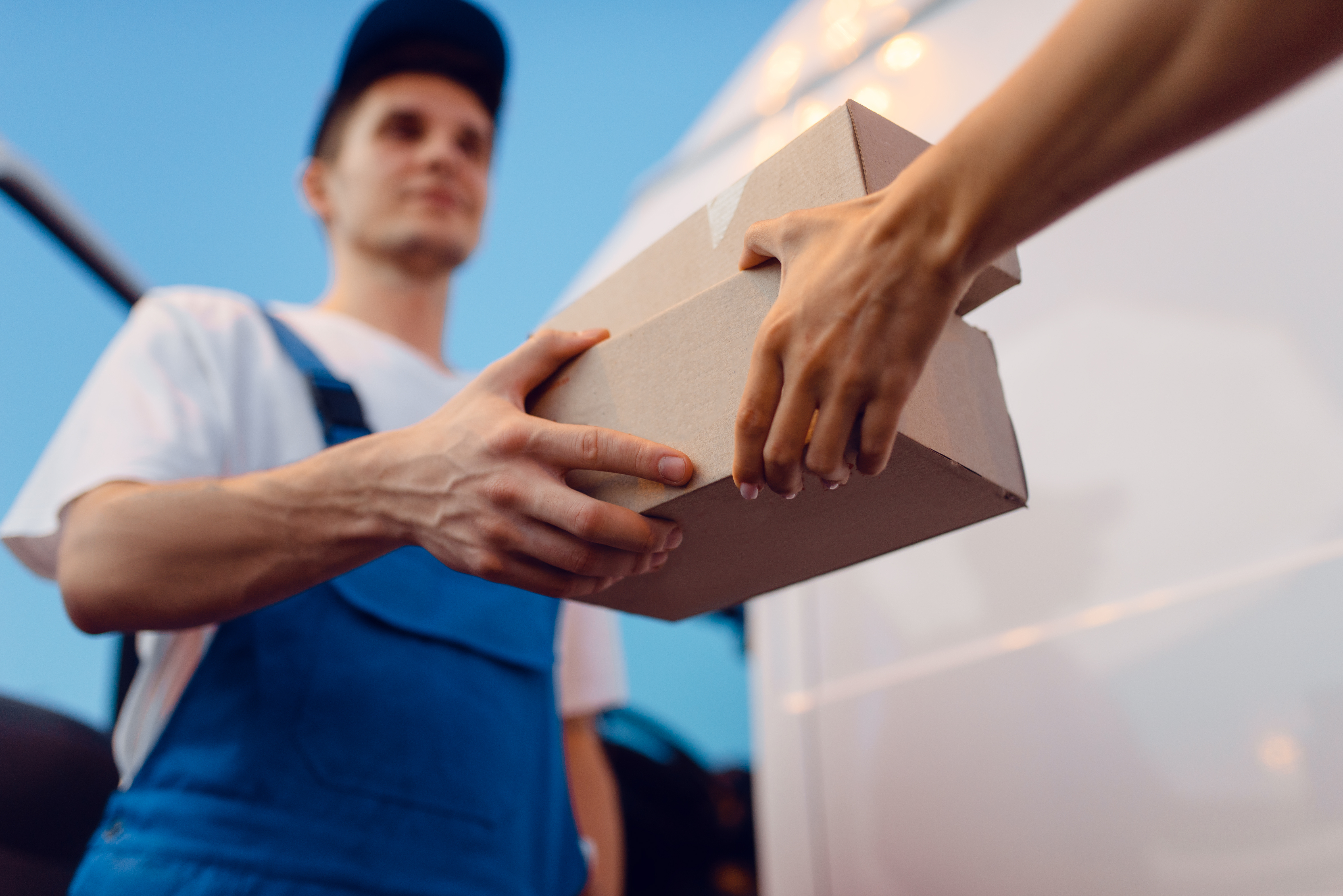 deliveryman-in-uniform-gives-parcel-to-female-recipient-at-the-car-delivery-service-man-holding-cardboard-package-near-the-vehicle-male-deliver-and-woman-courier-or-shipping-job